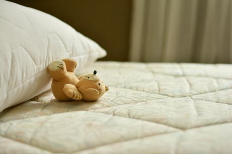 ベッドに寝転んだぬいぐるみのクマ
