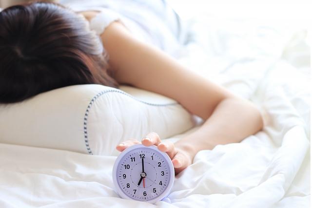 目覚ましを止める女性